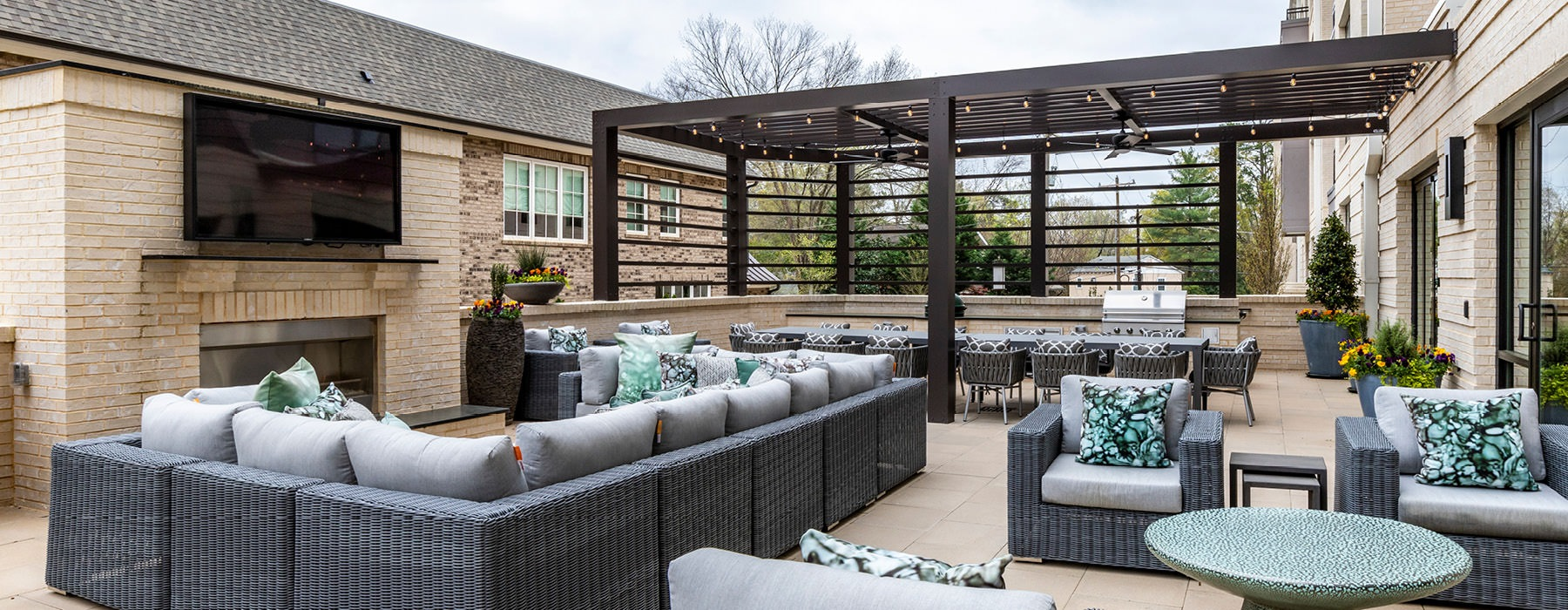 Outdoor grills with dining tables and fireplace.